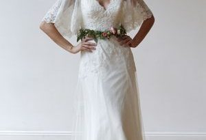 V-neck wedding dress with flutter sleeves and lace details by .